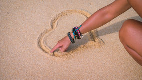 Female hand draw on the sand near the sea heart stock photography