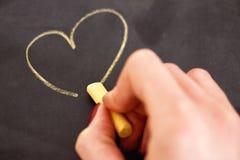 Female hand drawing heart on blackboard. Woman drawing heart on black stock images