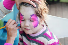 Female hand drawing purple butterfly on face Stock Image