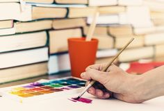 Female hand draws with a brush and watercolor paint on a sheet of paper on wooden table with stack of books background