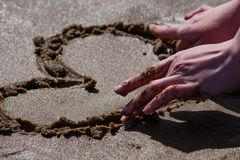 Female hand draws a heart on the sand of the beach. Is close stock photo