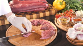 Female hand dressing steaks with black pepper. Two slices of pork meat on wooden board with vegetables and greens. stock footage