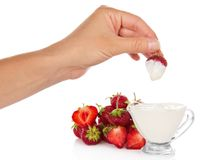 Female hand dunked strawberry into cup with cream Stock Photos