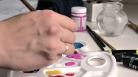Female hand dunks the brush in pink paint in the palette, then mixes it with white vector illustration