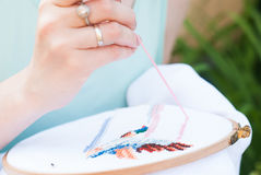 Female hand embroiders angels in the hoop. Royalty Free Stock Photos