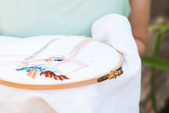 Female hand embroiders angels in the hoop. Royalty Free Stock Photography
