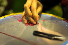 Female hand embroiders in the hoop under lamp light.  Stock Photos