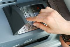 Female hand entering a secure PIN code at a cash point or ATM up close and in detail. A slender female hand entering a secure PIN code at a cash point or ATM up Stock Image
