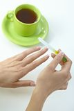 Female hand filing nails over cup of tea Stock Photography