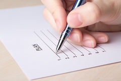 Female hand filling plan list with pen Royalty Free Stock Photo