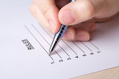 Female hand filling rules list with pen Royalty Free Stock Photos