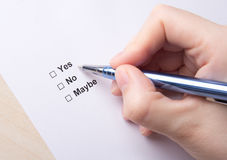 Female hand filling survey with yes, no, maybe answers. With pen Stock Images