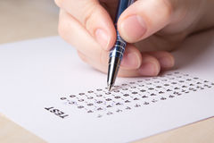 Female hand filling test score sheet with pen Royalty Free Stock Photo
