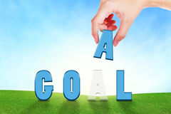 Female hand filling text Goal on grassland. Royalty Free Stock Photo