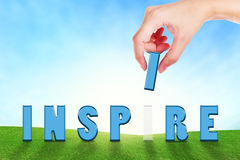 Female hand filling text inspire on grassland. Stock Images