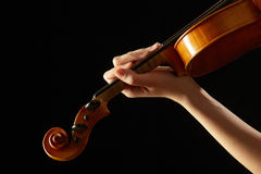 Female hand on the fingerboard violin. Isolated on black stock photography