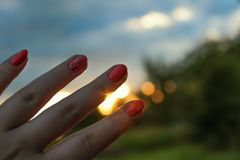 Female hand and fingers with manicure on a background of colorful sunset close up royalty free stock photography