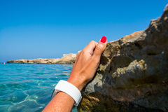 Female hand in a fitness tracker in azure seawater. Royalty Free Stock Images