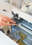 Female hand fixing sewing machine. Royalty Free Stock Photo