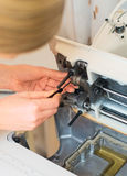 Female hand fixing sewing machine. Stock Photos