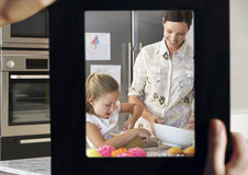 Female hand framing mother and daughter baking together in kitchen Royalty Free Stock Images