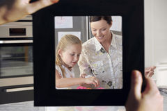 Female hand framing mother and daughter baking together in kitchen Stock Image
