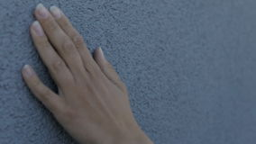 Female hand gently strokes the texture wall