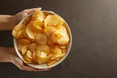 Female hand giving crispy potato chips bowl. Top view with copy space Royalty Free Stock Photos