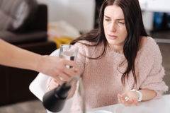 Female hand giving glass of water to her colleague Stock Photos