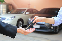 Female hand giving a key for buyer or rental car. Royalty Free Stock Photos