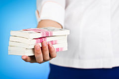 Female hand giving money pack on blue background. Royalty Free Stock Images