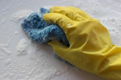 A female hand in a glove washes a surface with a rag with foam. Spring cleaning concept. stock photo