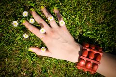Female hand on the grass, small daisy flowers Royalty Free Stock Photo