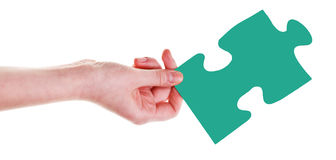 Female hand with green puzzle piece Stock Photo