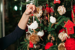 Female hand hang up toys on christmas tree Royalty Free Stock Photography
