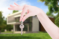 Female hand hanging house key as real estate concept Royalty Free Stock Images