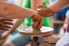 Female hand helping to make ceramic jug on a wheel children's hands. Royalty Free Stock Images
