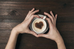 Female hand hold coffee cup with heart shape on wooden table. Top view royalty free stock image