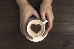 Female hand hold coffee cup with heart shape on wooden table. Top view royalty free stock photo