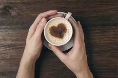 Female hand hold coffee cup with heart shape on wooden table. Top view stock photography