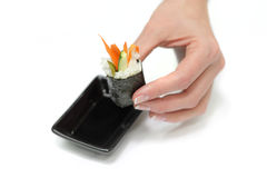 Female hand hold a Japan sushi and dip it to soy Stock Photography