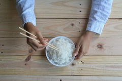 Female hand hold Rice in white bowl Stock Photos