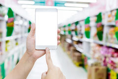 Female hand hold smartphone at supermarket and checking shopping Royalty Free Stock Photography