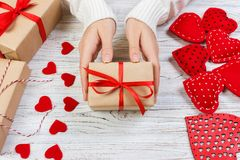 Free Female Hand Holding A Gift For Valentines Day, A Birthday Or Mother`s Day. Romantic White Wooden Background With Hearts And Gifts Stock Image - 106639631