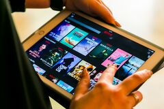 Free Female Hand Holding A Tablet Computer Using The Netflix Streaming App Royalty Free Stock Image - 183617006