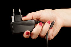 Female hand holding AC charger adapter Stock Photography
