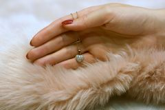 Female hand holding antique diamond heart pendant on dusty rose fur. Woman hand with red nails holding antiques white gold chain with heart shaped pendant with stock image