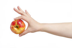 Female hand holding an apple with two fingers. In isolation. Stock Photography