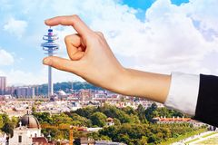 Female hand holding Arsenal Tower, Vienna, Austria. Optical illusion of woman`s hand holding Arsenal Tower between forefinger and thumb over Vienna scenic view royalty free stock image
