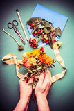 Female hand holding autumn flowers bunch and making fall flowers arrangements on table workspace with scissors , envelope and ribb Stock Images